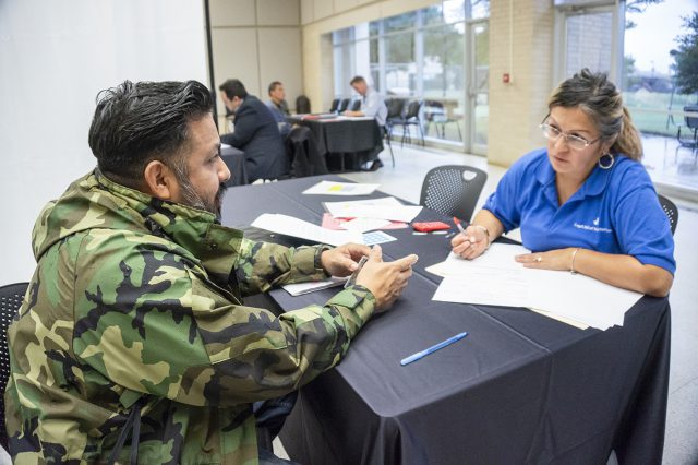Tarrant County attorney Elsa Marroquin takes down NW student Joseph Sonora's information during the Texas Lawyers for Texas Veterans Job Fair Oct. 19 on NW.