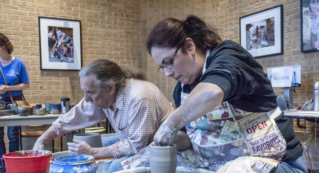 Continuing education instructor Ralph Tobin joined NE student Alison Cohen to make pottery at the Northeast Ceramics Art Pottery Sculptures table during Fall Fest Oct. 18. Hundreds attended the event despite rain moving it inside.
