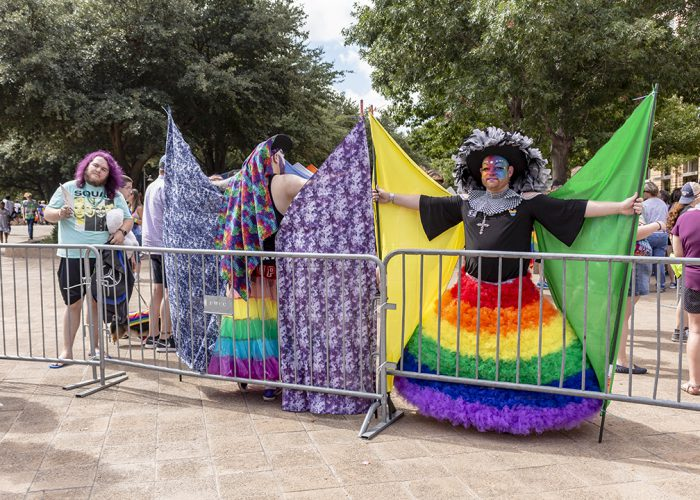 Two people from Dallas-Fort Worth Sisters of Perpetual Indulgence hold up flags they carried in the parade to shield festivalgoers from protesters Oct. 6.