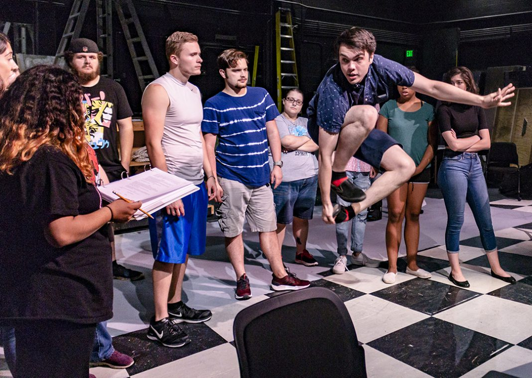 NE student Austin Peake, who plays Jesus in Godspell, rehearses a scene that involves him jumping over his leg to demonstrate a lesson to his disciples. The musical opens Oct. 16 and will run through Nov. 1 on NE.