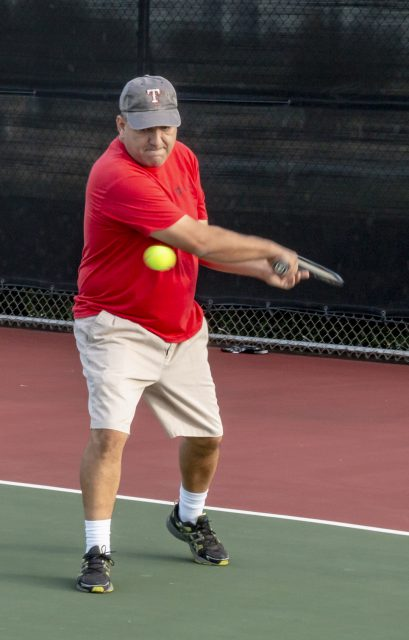 NW math instructor Alan Cazares backhands the ball during NW intramural tennis on Oct. 11.