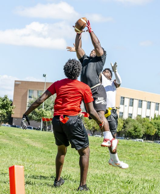 A SE student reaches for the sky to catch the ball while an opposing player attempts to intercept it during the intramural flag football championship on SE Campus.