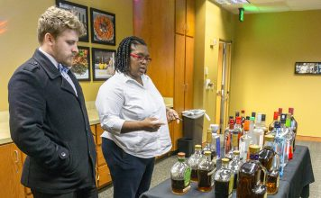 NE and SE student Sam Bailey and SE student Kemy Acosta peruse liquor bottles filled with colored water to inspire them for an assignment to create a unique concoction.