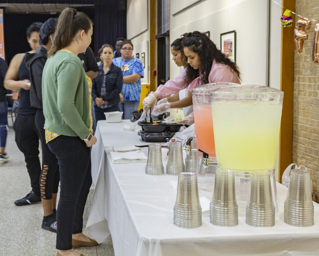 NE students, faculty and staff in attendance go through the line to get tacos as the event was part of the Let's Taco Bout It series.