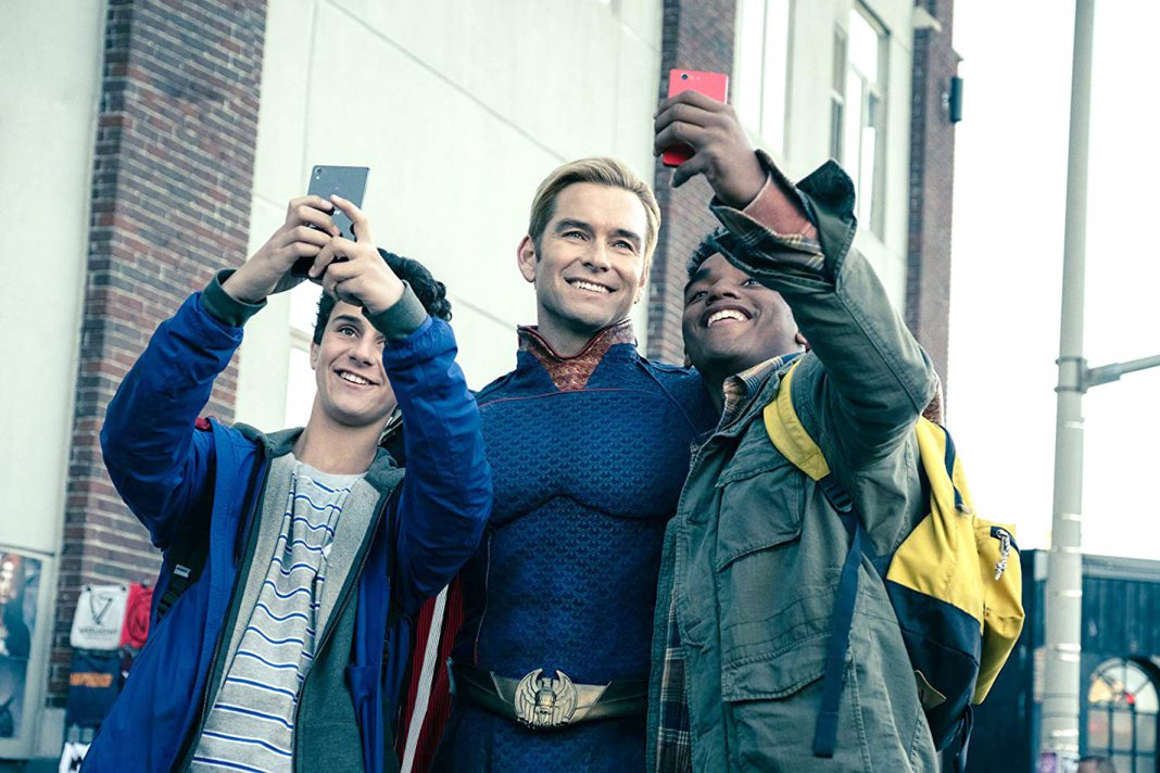 """Homelander, played byAnthony Starr, stands and poses with his young fans. He is the equivalent to this universe's Superman, and is the number one threat to """"The Boys"""" due to his superpowered abilities. Courtesy Amazon Studios/Photos by Jan Thijs"""