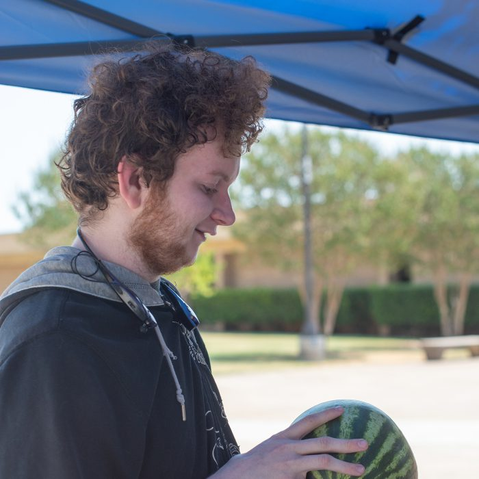 NE student Reece Laper attempts to guess the weight of a watermelon to win a prize during back to school activities. Photo by Joseph Serrata
