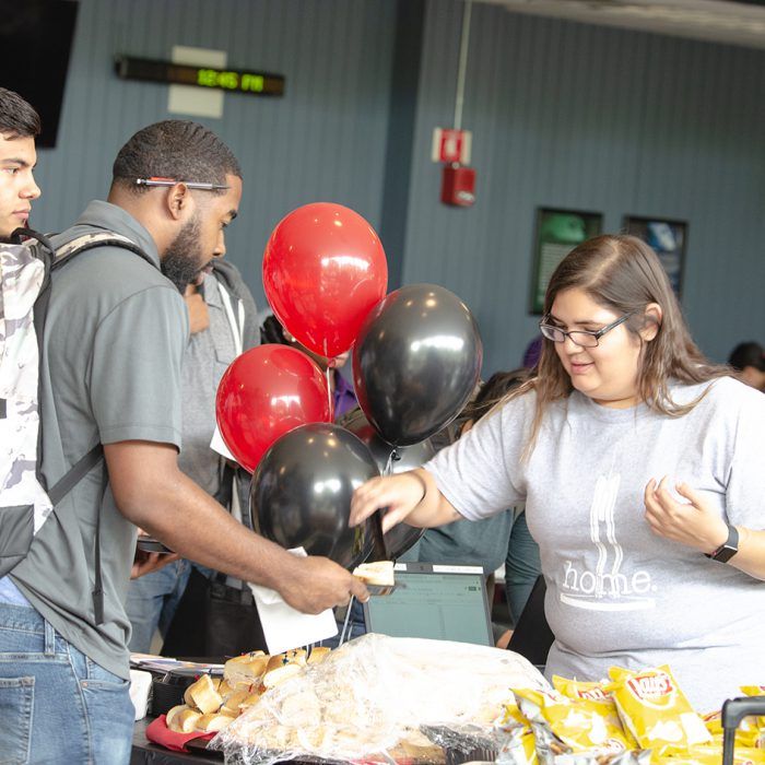 South student Naomi Felton passes out snacks and other goodies during the Toro Tailgate on South Campus. Students had the opportunity to learn about clubs and organizations. Photo by Kat Parker/The Collegian