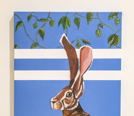 """Eddie Brassart's """"Hops"""" is an acrylic on canvas depicting a crouching rabbit gazing over its shoulder. Photo by Joseph Serrata/The Collegian"""