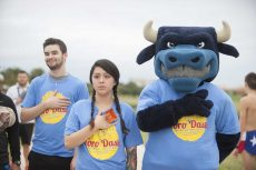 TR nursing administrative assistant Ruby Ann Rios stands with TCC's mascot Toro during the national anthem before the race Nov. 5. Photos by Peter Matthews/The Collegian