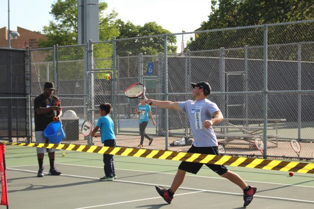 NE student David Schwartz runs to get to a ball while practicing hitting during a drill. Students from the NE Tennis Club volunteer with local children on Wednesdays.