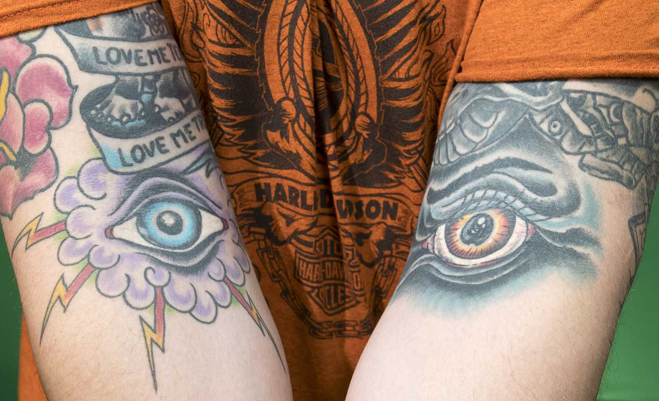 NE photography adjunct instructor Calen Barnum shows off his eye tattoos. On the left is a traditional American Glory eye, and on the right is an evil eye.