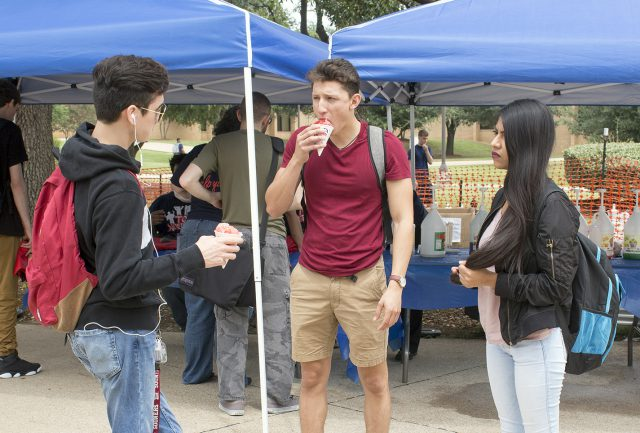 NE students Alan Soto and Jasive Valle enjoy free snowcones in the courtyard as part of the student activities welcome week event Monday Fun Day.
