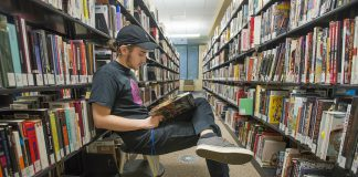 NW student Ashton Hinrjos sits and reads in the TR library while waiting to go to his next class.