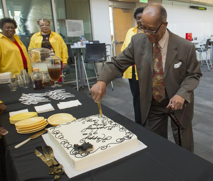 After speaking with attendees, former South professor Reby Cary cuts the cake to honor his 97th birthday Sept. 9.