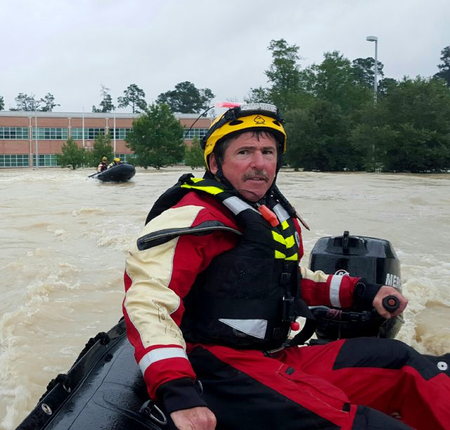 NW boat operator and squad officer Joe Short steers a boat through the flooding caused by Hurricane Harvey.