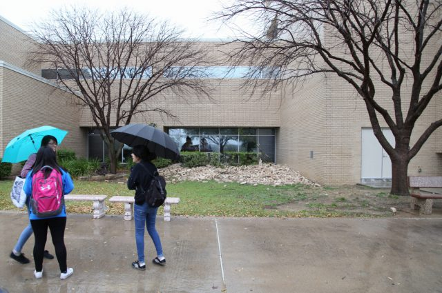Students look at the pile of bricks that were ripped from NW Campus' WSTU and WTLO buildings during a storm with heavy winds in March 2016. Twenty-one months later, an assessment is still being conducted.