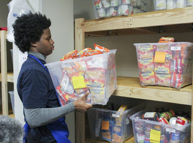 South student Isaiah Thompson places a bin of dry goods on the shelf at the South food pantry on Nov. 10. The pantry is located in SSTU 1104A-S.