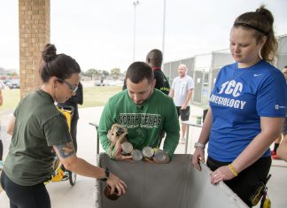 NE student Amanda Siefert and NE kinesiology workers Kenneth Gonzales and Morgan Ferguson drop off canned food donations that students were required bring to participate in the Turkey Trot.