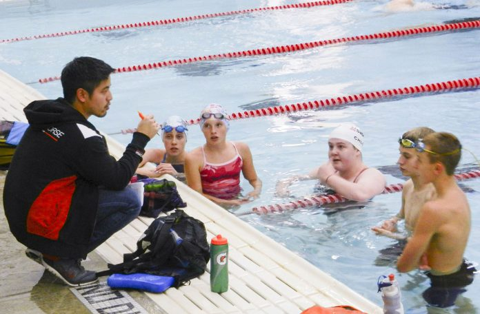 Sigma Swimmers founder and head coach Andrew Ha gives students instructions over technique during a practice session Nov. 9 at the NW pool.