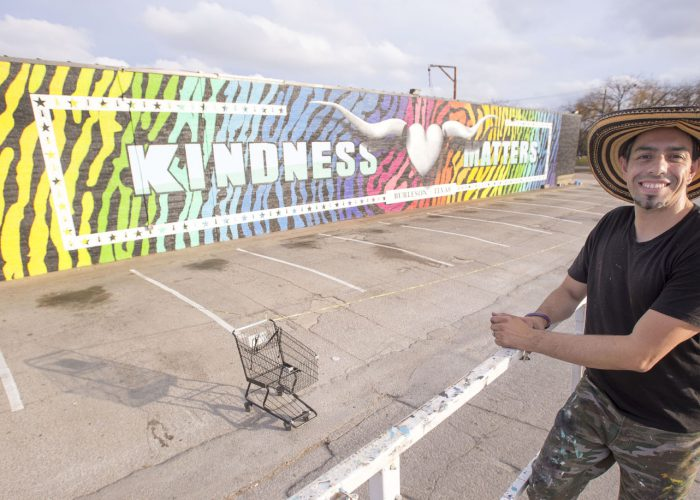 """TR Campus adjunct instructor Bernardo Vallarino poses with the finished project, """"Kindness Matters,"""" a mural representing symbols that relate to kindness and the community."""