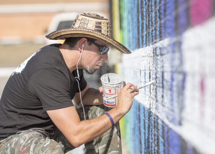 Vallarino uses a white exterior paint to complete the border on the mural he is working on outside of the Community Market in Burleson.