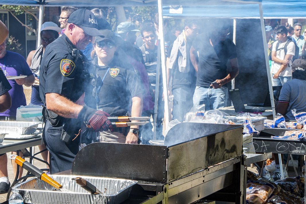 South Campus police officers dish up hot dogs and hamburgers as part of South's Cookout with the Cops event Oct. 4. The event is a way for students, faculty and staff to mingle with campus police officers.