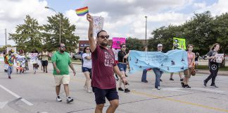 NE financial aid associate Andee Rodriguez waves a pride flag as he marches with other TCC students, faculty and staff carrying banners and posters during the Tarrant County Pride Parade Oct. 6 in downtown Fort Worth.