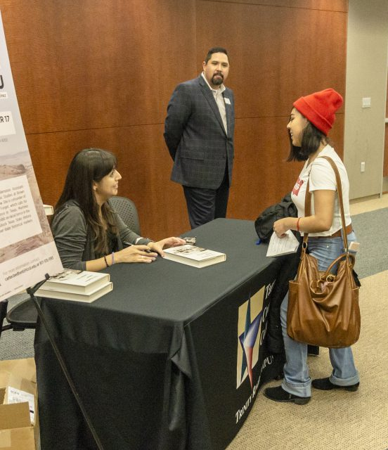 TR student Cindy Tovar gets her book signed by guest speaker Monica Munoz Martinez. Tovar was one of 20 attendees to receive a free copy.