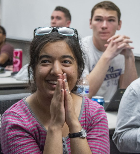 SE student Maryam Chowdry watches the 2018 midterm elections with anticipation as the results come up on the screen at an election watch party on SE.