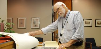 District archivist Thomas Kellam looks through the maps that are collected in the Heritage Room located in the J. Ardis Bell Library on NE Campus. Collegian file photo