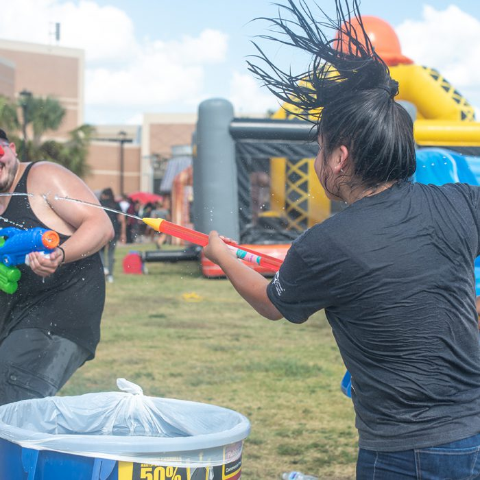 SE student Justin Hinton gets into a water gun fight with another student. There were a variety of activities on multiple campuses, such as dunk tanks, food and prizes for students to get back in the groove of the semester. Photo by Joseph Serrata/The Collegian